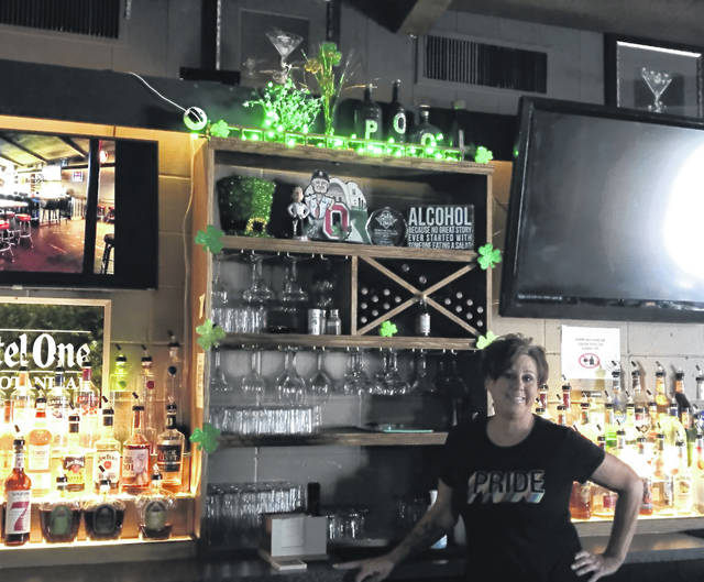 Christine Franklin stands behind the bar at Mulligans. Franklin worried she wouldn't be able to keep her bar open when Gov. Mike DeWine ordered dining rooms to close in March, but she's seen enough carryout business to stay operational until dining rooms reopened in May.