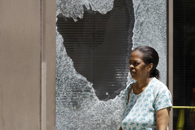 A woman walks past a broken window Monday, June 1, 2020, in downtown Cleveland. The City of Cleveland extended its curfew through Tuesday night after riots broke out on Saturday over the death of George Lloyd. (AP Photo/Tony Dejak)