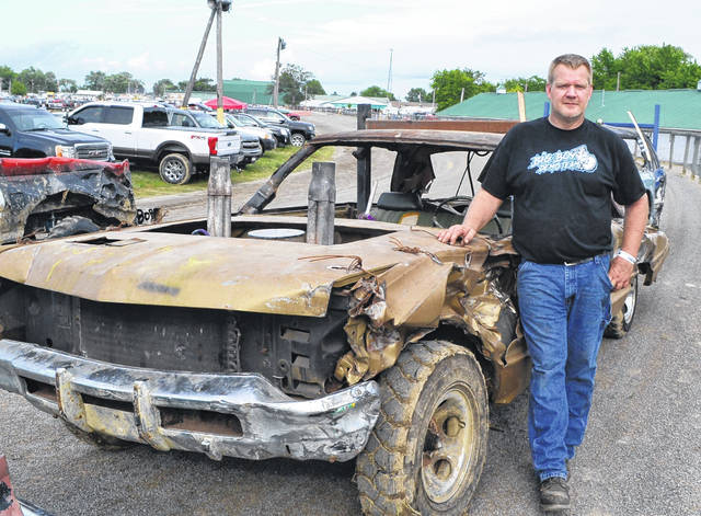 Brandon Meyer poses next to his 1968 Chrysler Imperial prior to Saturday night's demolition derby at the Putnam County Fair.