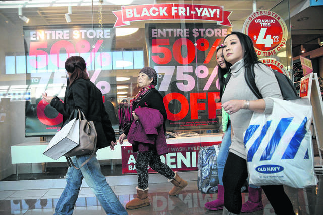 In this file photo, shoppers walk past a Black Friday advertisement at Cherry Hill Mall in Cherry Hill, N.J.
