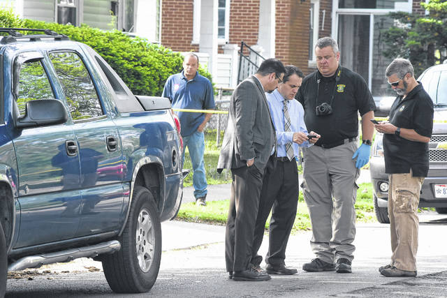 Two people were found inside the residence 0f 413 S. Atlantic, Lima, with gunshot wounds. A female was dead at the scene and a male died en route to the hospital. Assistant prosecutor Tony Miller, left, with Lima Police Detective Steve Stechchulte, officer Greg Adkins and Allen County Prosecutor Juergen A. Waldick examine the crime scene.
