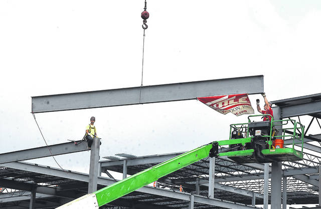 Iron workers Dylan Kleman, left, and Darren Siefker, are ready to set the final steel beam at Mercy Health-St. Rita's Graduate Medical Education Center on Wednesday. Kleman and Siefker are members of Iron Workers Local 290 in Dayton.
