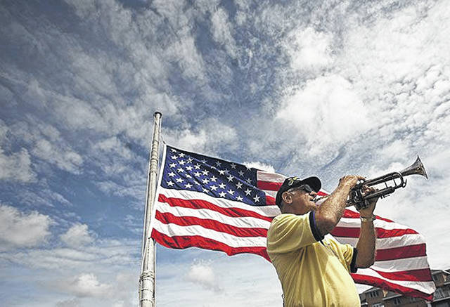 Mike Hodgis plays taps at the conclusion of the Memorial Day Service held aboard the decommissioned battleship Wisconsin in downtown Norfolk, Va., in May.