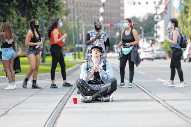 "A demonstrator, who identified himself as ""J"", sits in the street as demonstrators briefly block Loyola Ave. in downtown New Orleans, Tuesday, June 2, 2020, during a protest over the death of George Floyd, who died after being restrained by Minneapolis police officers on Memorial Day. (AP Photo/Gerald Herbert)"