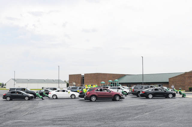 Graduates and their families gathered in the school parking lot for commencement.