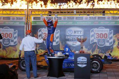 Chip Ganassi, left, looks on as Scott Dixon steps out of his cockpit and onto his car in Victory Lane after winning Saturday night's IndyCar race at Texas Motor Speedway in Fort Worth, Texas. (AP photo)