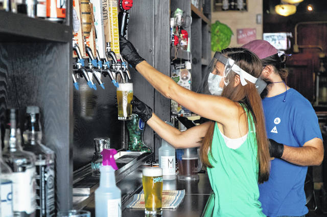 Owner Melani Domingues wears a visor to pour a beer on June 17 as The Green Lady bar reopens in Lakeview, Illinois.