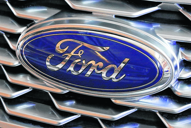 FILE- This Feb. 15, 2018, file photo shows a Ford logo on the grill of a 2018 Ford Explorer on display at the Pittsburgh Auto Show. Ford Motor Co. reports earnings Wednesday, April 25. (AP Photo/Gene J. Puskar, File)