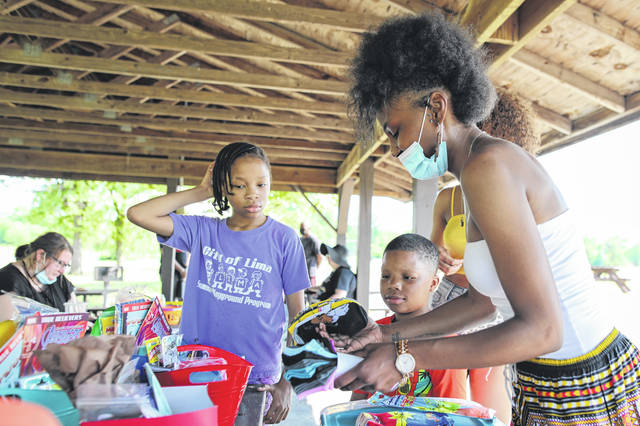 Eleven-year-old M'raya Nelson of Lima (left) and 11-year-old M'kye Nelson watch Sa'kiyha Matthews prepare prizes for the raffle drawings during the Juneteenth gathering held at Dr. Martin Luther King Jr. Center Park on Friday afternoon.