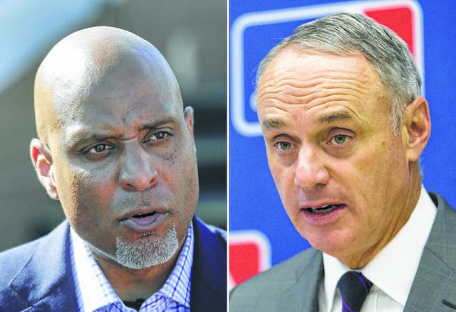 An email from major league baseball commissioner Rob Manfred (right) caused the Major League Baseball Players Association, led by Tony Clark (left) to call off a vote on the baseball owners' latest offer on Sunday.