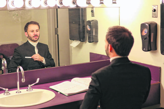 Conductor Andrew Crust adjusts his suit in his dressing room before he performs with the Lima Symphony Orchestra in January. The symphony announced Thursday that Crust was its new conductor.