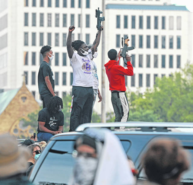 Men show off their automatic weapons during the protests over the death of George Floyd around the Ohio Statehouse building in Columbus on Sunday.