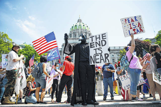 FILE - In this Friday, May 15, 2020 file photo, protesters hold a rally against Pennsylvania's coronavirus stay-at-home order at the state Capitol in Harrisburg, Pa.