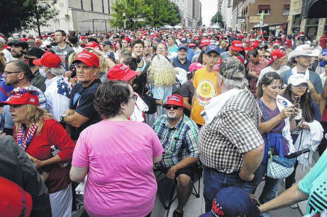 People wait in downtown Tulsa, Okla., to enter President Donald Trump's campaign rally on Saturday, June 20, 2020.