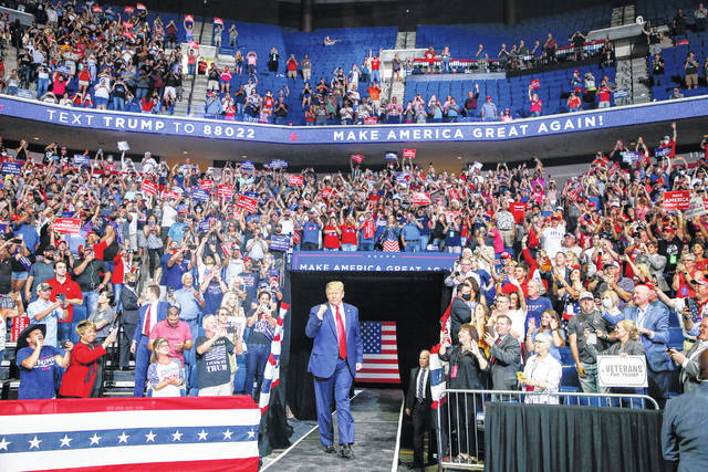 President Donald Trump, center, walk toward the stage while supporters cheer during his campaign rally at BOK Center in Tulsa, Okla., Saturday, June 20, 2020.