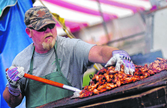 Tom Shipman, of Lima, helps cook the wings Saturday during the annual St. Gerard Parish Festival.
