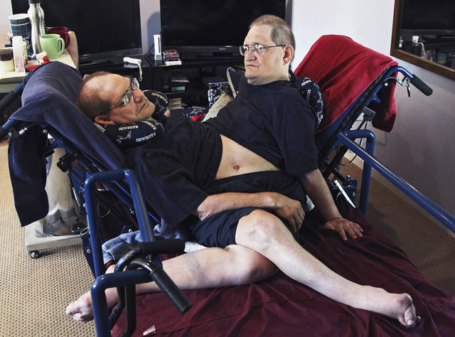 FILE - Donnie, left, and Ronnie Galyon sit inside their Beavercreek, Ohio, home, in a Wednesday, July 2, 2014 file photo. The world's longest surviving conjoined twins died on July 4, 2020 at the age of 68. Ronnie and Donnie Galyon of Beavercreek, Ohio were born joined at the abdomen. In 2014, earned the distinction of being the world's oldest set of conjoined twins shortly before their 63rd birthday. (Drew Simon/Dayton Daily News via AP, File)