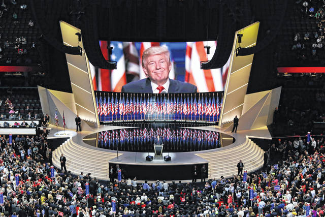 Republican presidential candidate Donald Trump smiles from a large screen July 21, 2016, as he addresses delegates during the final day session of the Republican National Convention in Cleveland. After months of insisting that the Republican National Convention go off as scheduled despite the coronavirus pandemic, Trump is adapting plans due to the coronavirus pandemic.
