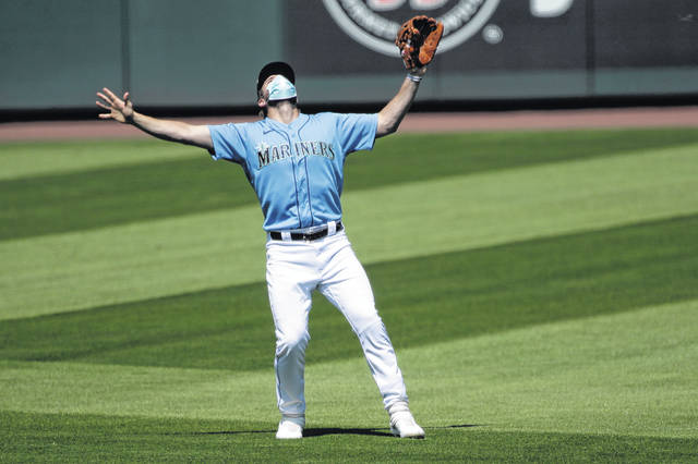 "Seattle Mariners' third baseman Patrick Wisdom wears a mask as he waves off other players to make a catch, Friday, July 10, 2020, during a ""summer camp"" baseball scrimmage game in Seattle. (AP Photo/Ted S. Warren)"