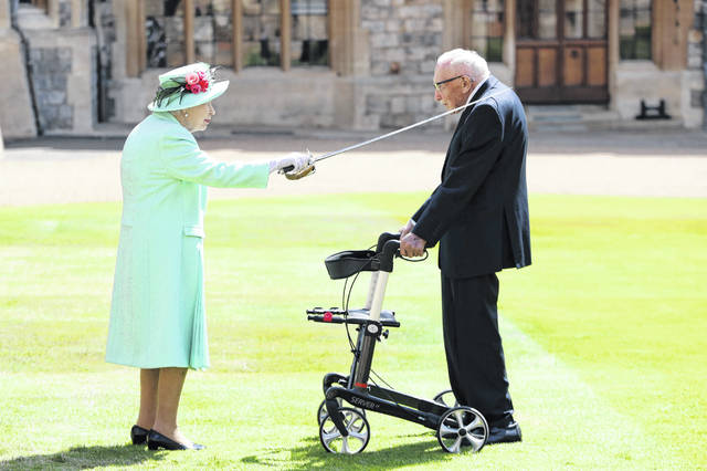 Captain Sir Thomas Moore receives his knighthood from Britain's Queen Elizabeth, during a ceremony at Windsor Castle in Windsor, England, on Friday. He raised nearly $40 million for health service charities by walking laps of his Bedfordshire garden.