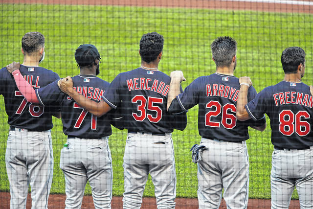 Members of the Cleveland Indians line up for the national anthem before an exhibition baseball game against the Pittsburgh Pirates in Pittsburgh, Saturday, July 18, 2020. (AP Photo/Gene J. Puskar)