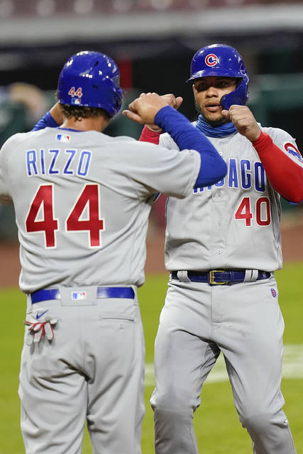 Chicago Cubs' Anthony Rizzo (44) and Willson Contreras (40) celebrate after they each scored a run in the first inning of a baseball game against the Cincinnati Reds at Great American Ballpark in Cincinnati, Monday, July 27, 2020. (AP Photo/Bryan Woolston)