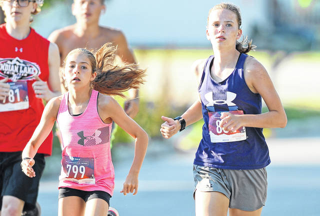 Jackson Center's Alaina Mann, 13, left, and Spencerville's Lillee Stewart run in Saturday's 5K on the Lake at Lakeview. Mann was the top female finisher.