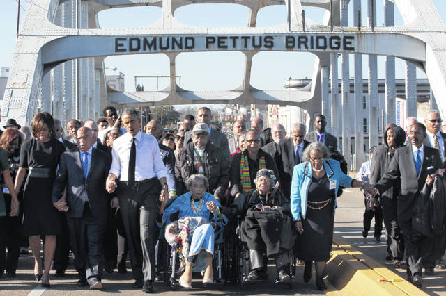 """FILE - In this March 7, 2015, file photo, singing """"We Shall Overcome,"""" President Barack Obama, third from left, walks holding hands with Amelia Boynton, who was beaten during """"Bloody Sunday,"""" as they and the first family and others including Rep. John Lewis, D-Ga, left of Obama, walk across the Edmund Pettus Bridge in Selma, Ala., for the 50th anniversary of """"Bloody Sunday,"""" a landmark event of the civil rights movement. Some residents in the landmark civil rights city of Selma, Ala., are among the critics of a bid to rename the historic bridge where voting rights marchers were beaten in 1965."""