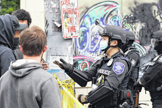 """A police officer engages with a protester Wednesday, July 1, 2020, in Seattle, where streets had been blocked off in an area demonstrators had occupied for weeks. Seattle police showed up in force earlier in the day at the """"occupied"""" protest zone, tore down demonstrators' tents and used bicycles to herd the protesters after the mayor ordered the area cleared following two fatal shootings in less than two weeks. The """"Capitol Hill Occupied Protest"""" zone was set up near downtown following the death of George Floyd while in police custody in Minneapolis."""