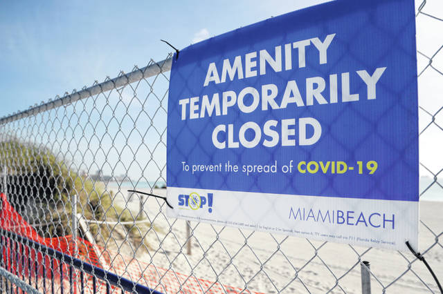 A sign is posted at a closed entrance to the beach during the new coronavirus pandemic, Friday, July 3, 2020, in the South Beach neighborhood of Miami Beach, Fla. Beaches throughout South Florida are closed for the busy Fourth of July weekend to avoid further spread of the new coronavirus.