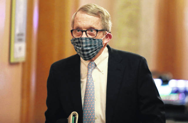 Ohio Gov. Mike DeWine wears a protective mask made by his wife as he walks into an April coronavirus news conference at the Ohio Statehouse in Columbus.