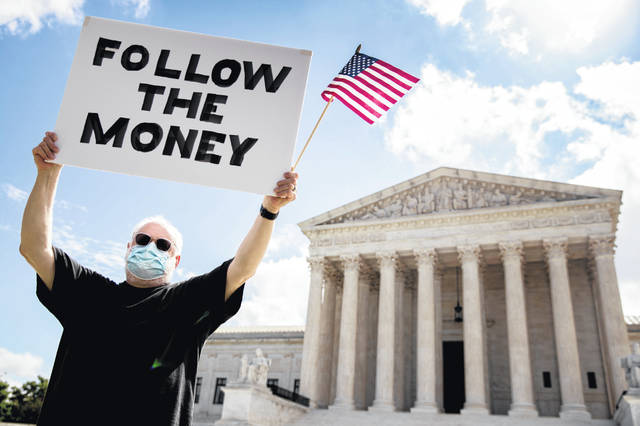 """Bill Christeson holds up a sign that reads """"Follow the Money"""" outside the Supreme Court, Thursday, July 9, 2020, in Washington. The Supreme Court ruled Thursday that the Manhattan district attorney can obtain Trump tax returns while not allowing Congress to get Trump tax and financial records, for now, returning the case to lower courts."""