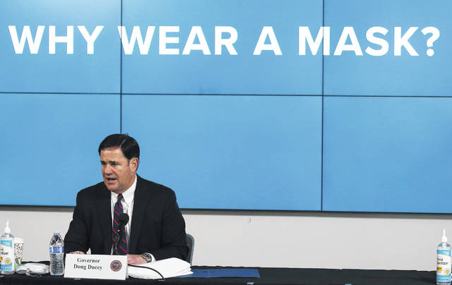 FILE - In this Thursday, July 9, 2020, file photo, Arizona Republican Gov. Doug Ducey speaks about the latest coronavirus update in Arizona and benefits of wearing a mask during a news conference in Phoenix. With the coronavirus spreading out of control and Arizona cities just beginning to require residents to wear masks in public last month, a few hundred people gathered in Scottsdale to make clear they did not approve of the heavy hand of government telling them to cover their faces.