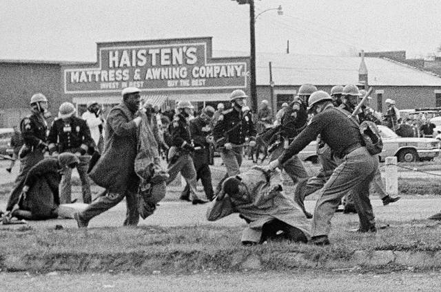 FILE - In this March 7, 1965, file photo, a state trooper swings a billy club at John Lewis, right foreground, chairman of the Student Nonviolent Coordinating Committee, to break up a civil rights voting march in Selma, Ala. Lewis sustained a fractured skull. Lewis, who carried the struggle against racial discrimination from Southern battlegrounds of the 1960s to the halls of Congress, died Friday, July 17, 2020.