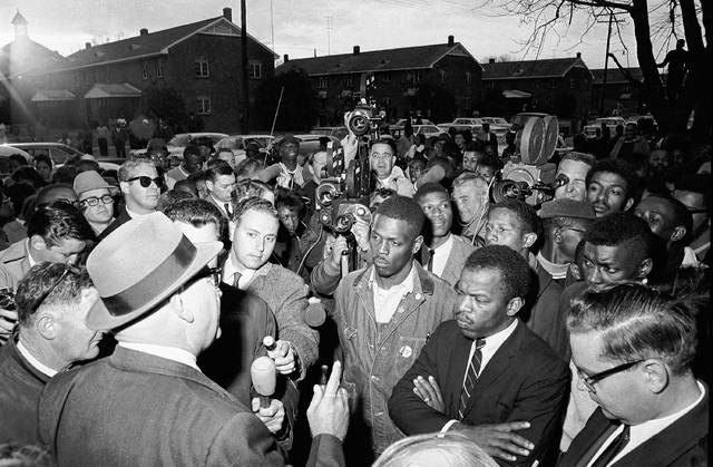 FILE - In this Feb. 23, 1965, file photo, Wilson Baker, left foreground, public safety director, warns of the dangers of night demonstrations at the start of a march in Selma, Ala. Second from right foreground, is John Lewis of the Student Non-Violent Committee. Lewis, who carried the struggle against racial discrimination from Southern battlegrounds of the 1960s to the halls of Congress, died Friday, July 17, 2020.