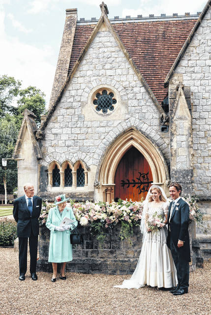 In this photograph released by the Royal Communications of Princess Beatrice and Edoardo Mapelli Mozzi, Britain's Queen Elizabeth II and Prince Philip stand alongside Princess Beatrice and Edoardo Mapelli Mozzi outside The Royal Chapel of All Saints at Royal Lodge, Windsor, England, after their wedding on Saturday July 18, 2020. Princess Beatrice wore a vintage dress loaned to her by Queen Elizabeth II at her wedding, Buckingham Palace said Saturday as it released official photographs from the small family event.