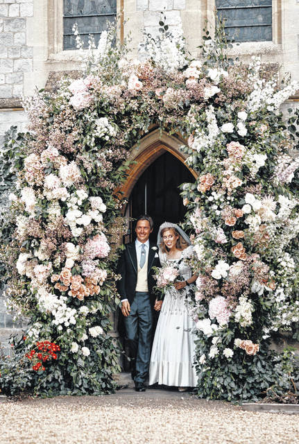 In this photograph released by the Royal Communications of Princess Beatrice and Edoardo Mapelli Mozzi, Britain's Princess Beatrice and Edoardo Mapelli Mozzi stand in the doorway of The Royal Chapel of All Saints at Royal Lodge, Windsor, England, after their wedding on Saturday July 18, 2020. Princess Beatrice wore a vintage dress loaned to her by Queen Elizabeth II at her wedding, Buckingham Palace said Saturday as it released official photographs from the small family event.