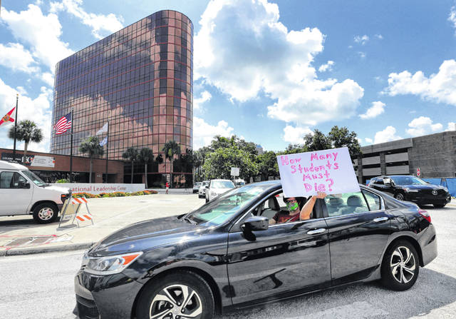 FILE - In this Tuesday, July 7, 2020 file photo, a teacher holds up a sign while driving by the Orange County Public Schools headquarters as educators protest in a car parade around the administration center in downtown Orlando, Fla. As pressure mounts for teachers to return to their classrooms this fall, concerns about the pandemic are pushing many toward alternatives, including career changes, as some mobilize to delay school reopenings in areas hardest hit by the coronavirus. Teachers unions have begun pushing back on what they see as unnecessarily aggressive timetables for reopening.