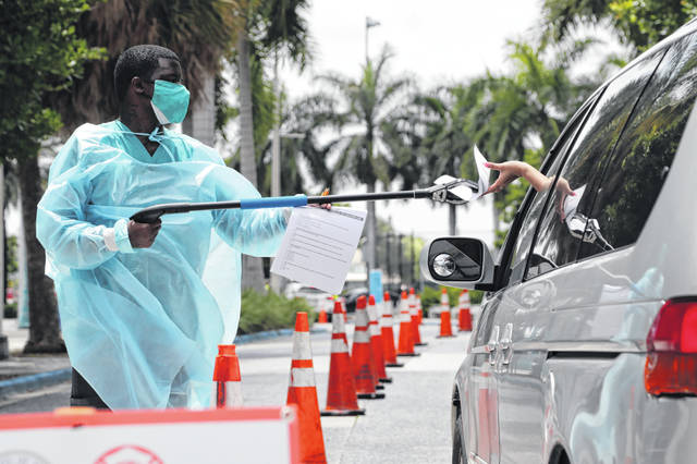 Healthcare worker Dante Hills, left, passes paperwork to a woman in a vehicle at a COVID-19 testing site outside of Marlins Park, Monday, July 27, 2020, in Miami. The Marlins home opener against the Baltimore Orioles on Monday night has been postponed as the Marlins deal with a coronavirus outbreak that stranded them in Philadelphia.