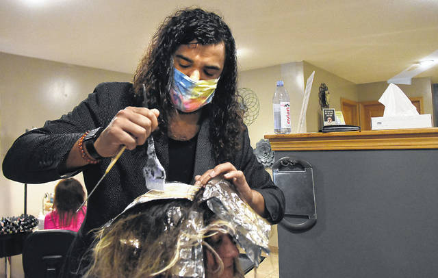Timothy Wannemacher, a stylist at Angels Family Hair Salon in Lima, highlights a customer's hair.