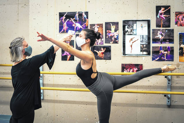 Out on a Limb Dance school director Amber Keeley take sthe temperature of dancer Olivia Brockman, 15, before a dance class on July 9 in St. Paul, Minn. People taking advantage of service businesses may find themselves signing more liability waivers amid the coronavirus pandemic.