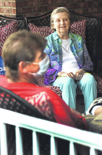 Mike Connor, left, of Lima, visits with his mother, Betty Ray, at Liberty Retirement Community of Lima during an open-air visitation Monday. Ray is the owner of the Edgewood Skate Arena, and Connor is the manager. Connor comes to visit his mother daily outside her window. Monday was the first day he could schedule a porch since the coronavirus pandemic hit.