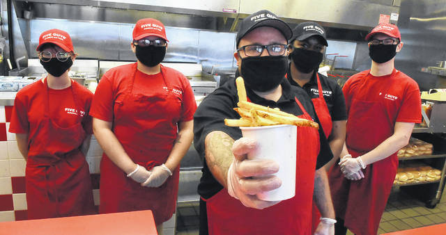 Five Guys manager Benjamin Davis holds up the restaurant's fan-favorite fries with staff members.