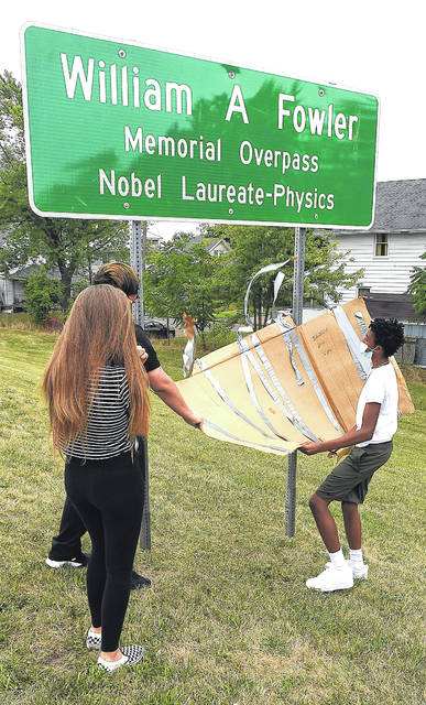 South Science and Technology Magnet School students, from left, Hailey Hahn, 14, Gavin Capuchino, 15, and Lee Hogan, 14, unveil the William A. Fowler Memorial Overpass sign on Thursday. The eighth-grade class at South worked to name something in the city after the Nobel Prize winner, who grew up in a brick house that can be seen from the overpass.