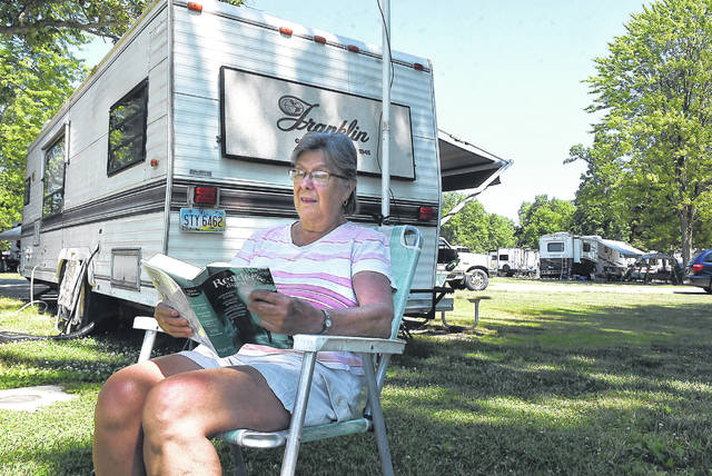 Betty Wharton, of Lima, enjoys a book while camping at Indian Lake State Park with her family.