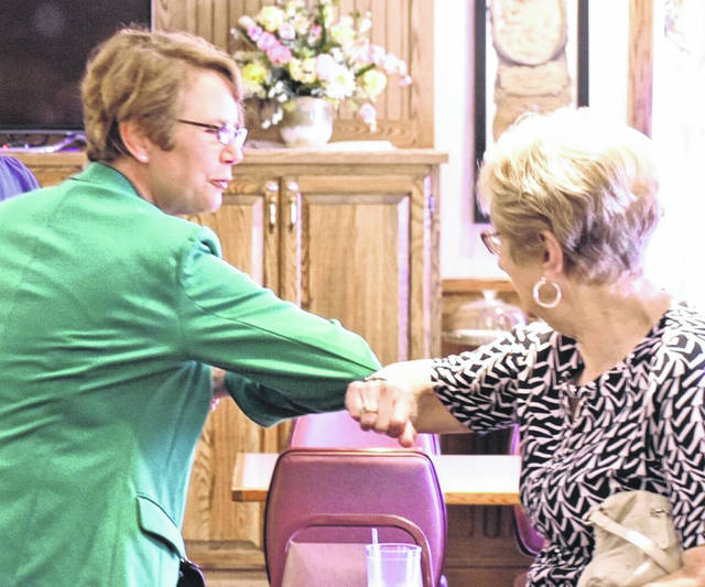Foregoing the traditional handshake amid the COVID-19 pandemic, Ohio Supreme Court Associate Justice Sharon Kennedy exchanges an elbow-bump with a Putnam County resident during a noon luncheon hosted by the Ottawa Chamber of Commerce on Tuesday.