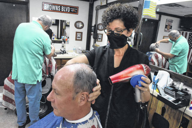 Jeni Armentrout uses a blowdryer on Mike Haney while working at Northland Barbers in Lima.