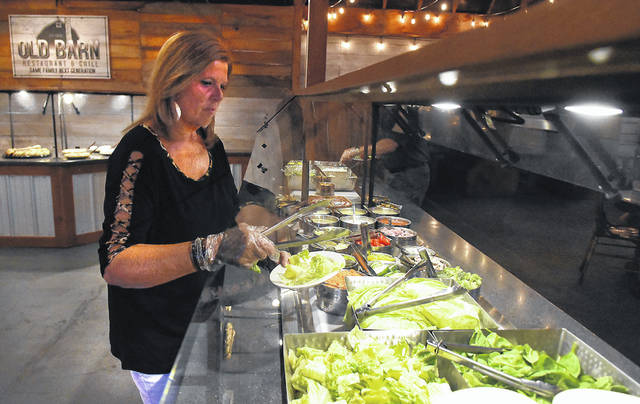 Vickie Groves, of Wapakoneta, makes a salad at the buffet at Old Barn Restaurant & Grill in Lima.