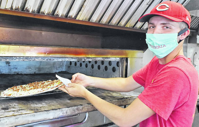 Zach Shafer, the manager of The Pizzeria location in Ottawa, puts a pizza in the oven.