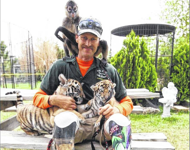 John Reinke poses with two tiger cubs and his pet monkey.